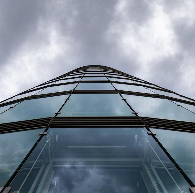 Colpo di angolo basso di un grattacielo in una facciata di vetro sotto le nuvole di tempesta