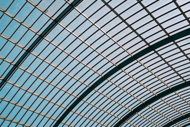 Colpo di angolo basso di un tetto di vetro di un edificio moderno sotto il cielo blu