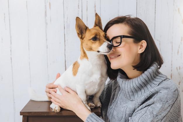 Colpo di attraente giovane donna abbraccia il suo cane preferito, tocca con il naso, esprime grande amore per gli animali domestici. il cane leale ha buoni rapporti con l'ospite. amicizia, relazioni, animali e persone