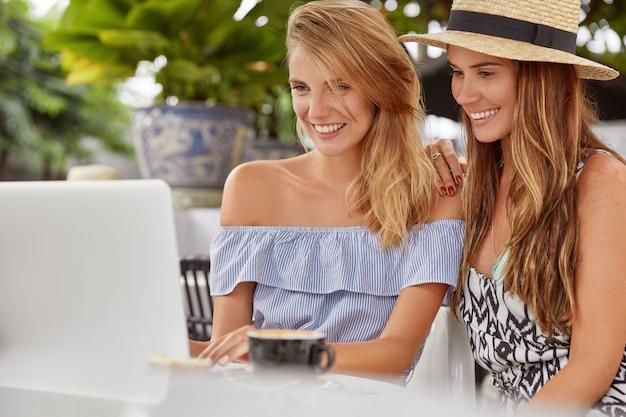Colpo di belle donne che trascorrono la pausa caffè insieme, si siedono davanti al laptop aperto, inviano messaggi con gli amici nei social network o fanno acquisti online, godono del bel tempo estivo. persone e tecnologia