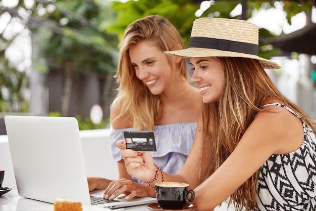Colpo di donne soddisfatte effettua il pagamento online durante il pranzo al bar con terrazza, la tastiera del computer portatile, tiene la carta di plastica. coppia lesbica naviga in internet e nei negozi web, beve cappuccino o latte
