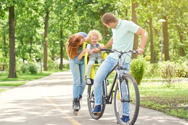 Colpo di genitori felici coccole con il loro bambino mentre in bicicletta e pattinaggio insieme al parco amore affetto famiglia affetto genitori emozioni infanzia stile di vita attivo.