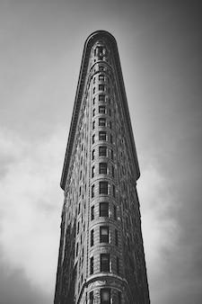 Colpo di gradazione di grigio di angolo basso del curioso edificio di flatiron a manhattan, new york, usa