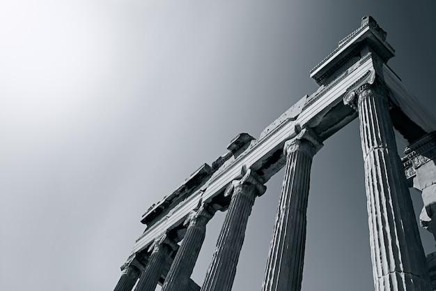 Colpo di gradazione di grigio di angolo basso di un tempio romano antico sotto il sole luminoso
