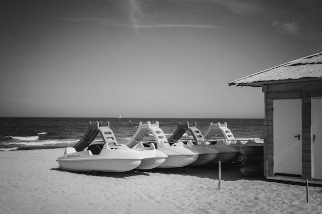 Colpo di gradazione di grigio di natanti o imbarcazioni marine vicino a una cabina su una spiaggia sabbiosa