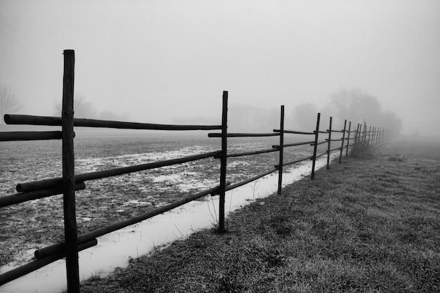Colpo di gradazione di grigio di una rete fissa in un campo in mugla in turchia durante il tempo nebbioso