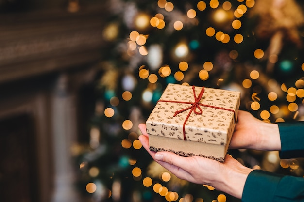 Colpo di hirizontal di bella scatola attuale avvolta in mani del `s della donna contro l'albero decorato del nuovo anno o di natale