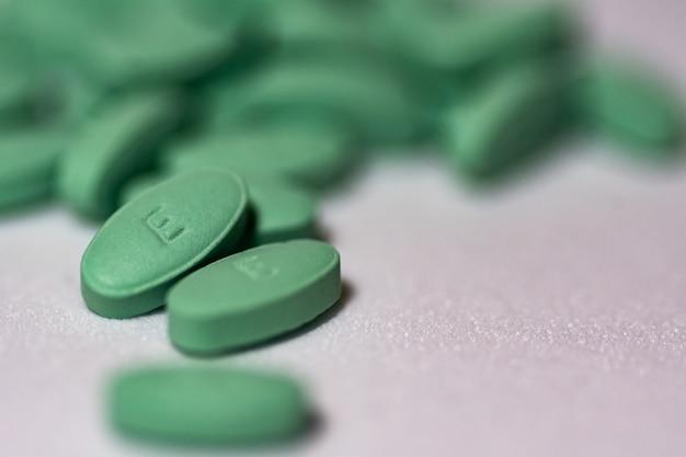 Colpo di messa a fuoco selettiva di pillole verdi su una superficie bianca
