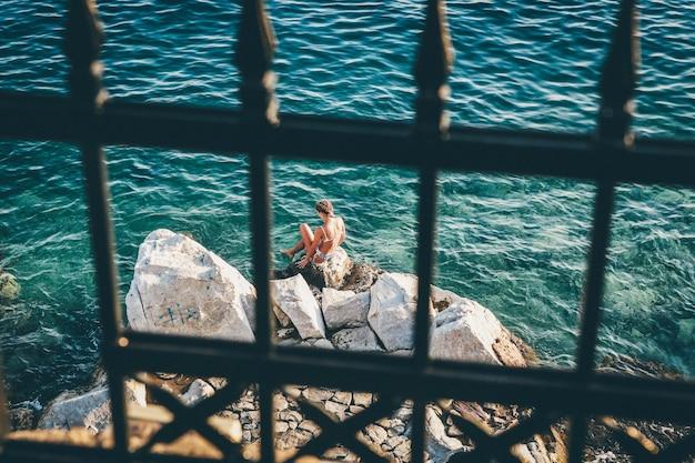 Colpo di messa a fuoco selettiva di un bikini femminile che si siede su una roccia dal corpo idrico
