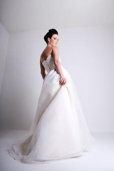 Colpo di moda di bella giovane sposa vestita in abito da sposa bianco