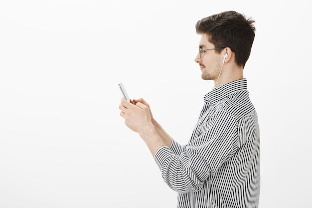 Colpo di profilo di fiducioso attraente ragazzo barbuto in occhiali alla moda e camicia a righe, tenendo lo smartphone e guardando lo schermo
