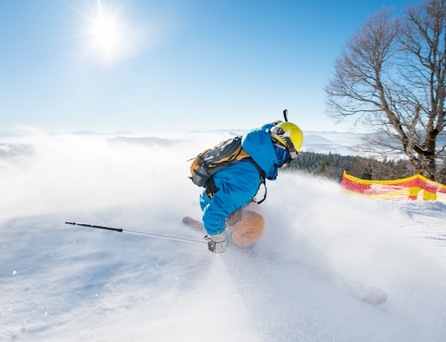 Colpo di retrovisore di uno sciatore freerider che scivola giù per il pendio alle montagne della stazione sciistica