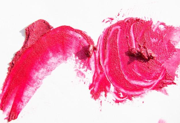Colpo di rossetto lucido rosa con madreperla isolato su sfondo bianco