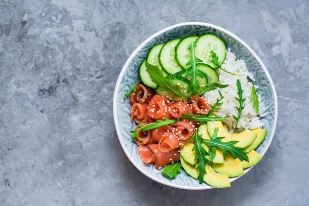 Colpo di salmone con avocado, rucola e cetriolo in una ciotola. vista dall'alto. copia spazio