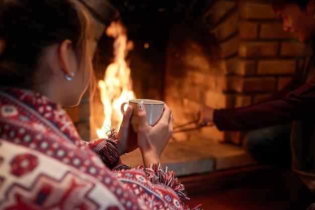 Colpo di spalla di una donna che si scalda le mani sulla tazza di tè caldo seduto davanti al caminetto, il suo ragazzo si occupa di carbone