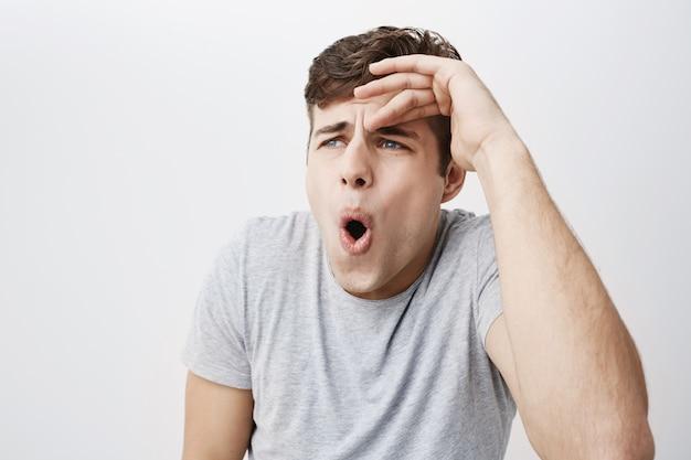 Colpo di studio di eccitato maschio caucasico scioccato vestito con una maglietta grigia con espressione sorpresa, scopre notizie inaspettate, dice davvero? emotivo uomo europeo imbronciato le labbra per l'eccitazione