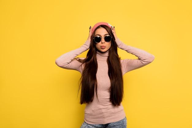 Colpo di studio indoor di donna elegante alla moda con lunghi capelli scuri che indossa il cappello rosa e occhiali neri vista frontale della donna felice