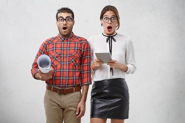 Colpo di studio isolato di sorpreso femmina e maschio in occhiali e abiti formali