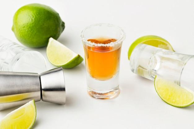 Colpo di tequila ad alto angolo con fette di lime