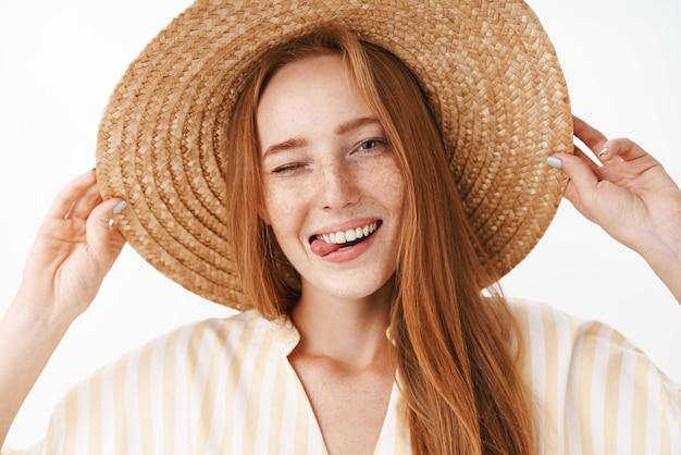 Colpo di testa di gioiosa femmina rossa attraente in cappello di paglia con le lentiggini che sbattono le palpebre felicemente e spuntavano lingua godendo soleggiata calda giornata estiva in vacanza camminando sulla spiaggia sorridente ampiamente
