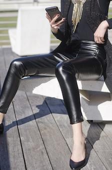 Colpo di una femmina seduta mentre si tiene un telefono indossando pantaloni di pelle nera e collana d'oro
