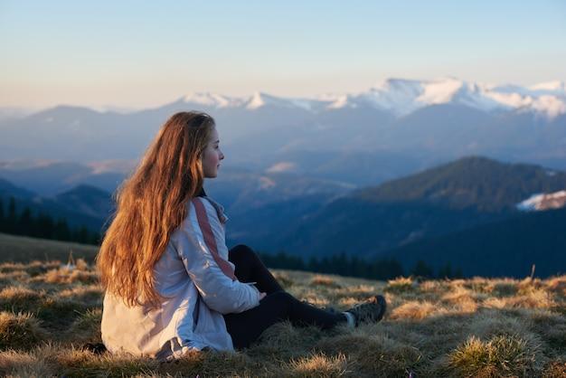 Colpo di una giovane donna seduta sulla cima di una montagna
