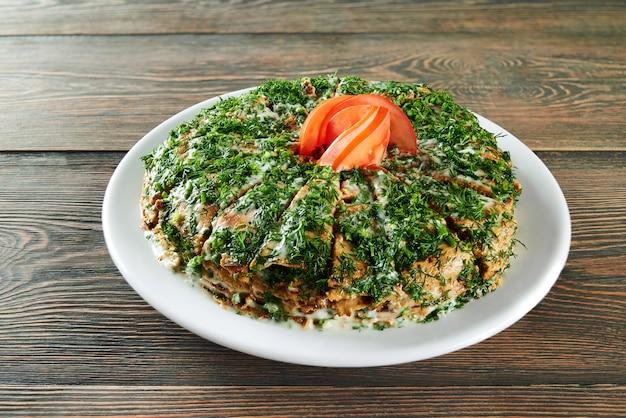Colpo di una pila di frittelle affettato e decorato con verdure e pomodoro in cima servito sul tavolo di legno al ristorante che mangia cibo delizioso menu ricetta cucina cucinare.