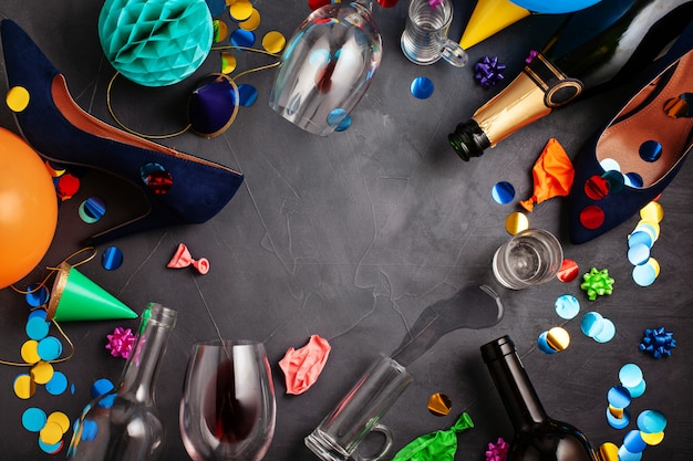 Colpo di vista dall'alto di dopo una celebrazione della festa con bottiglie vuote, bicchiere di vino, scarpe da ragazza e accessori per feste