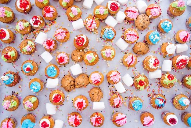 Colpo di vista superiore di molti gustosi cupcakes colorati su sfondo bianco