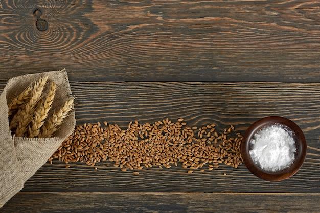 Colpo di vista superiore di un mazzo di grano e di sale del miglio sugli ingredienti alimentari di legno del copyspace del piano di lavoro che cucinano concetto sano tradizionale di nutrizione di cottura del forno di ricetta.