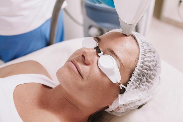 Colpo di vista superiore di una donna matura che ottiene trattamento facciale di depilazione del laser una clinica di bellezza