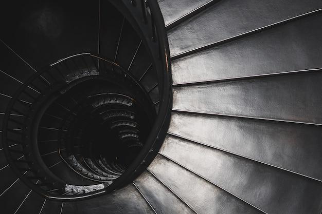 Colpo di vista superiore in scala di grigi della scala a chiocciola - concetto di mistero