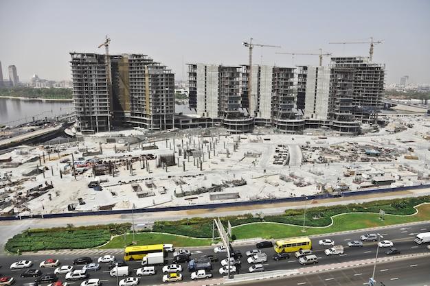 Colpo distante di un'area urbana con le automobili sulla strada e gli edifici alti