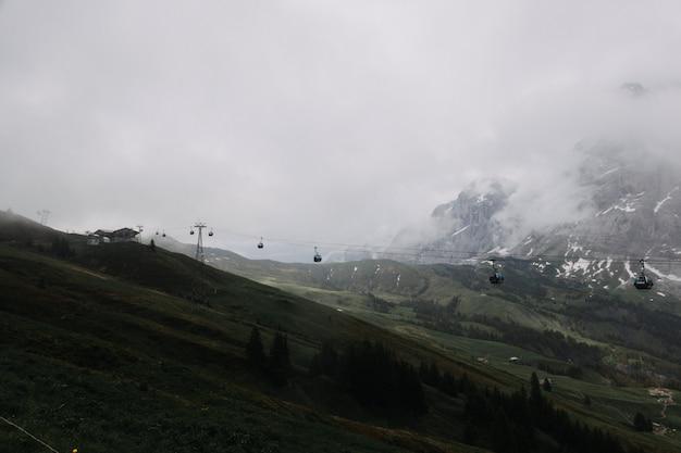 Colpo distante di una teleferica vicino alle montagne circondate dagli alberi