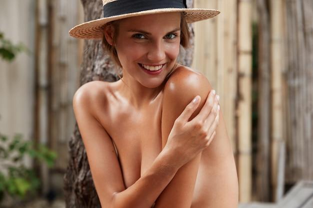 Colpo esterno di bella donna sorridente con un corpo snello perfetto, si nasconde come nuda, indossa un cappello estivo alla moda, posa da sola.