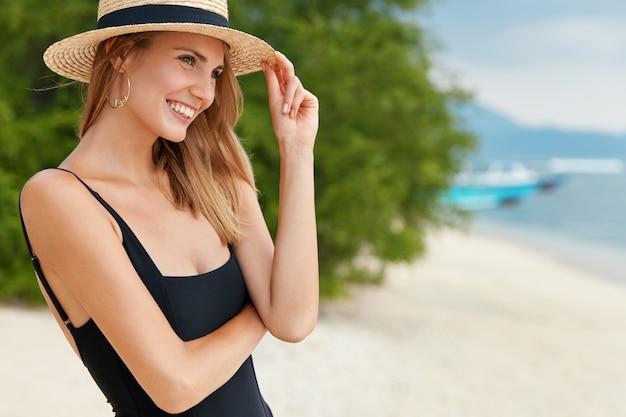 Colpo esterno di donna snella con espressione positiva, vestita in bikini nero e cappello di paglia, guarda in lontananza come si trova vicino all'oceano, ammira le onde morbide e il sole. concetto di estate e resort