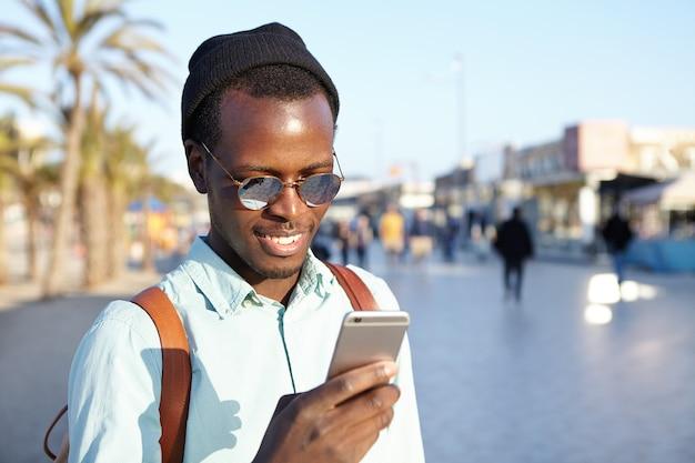 Colpo esterno di sorridente allegro giovane viaggiatore utilizza lo smartphone