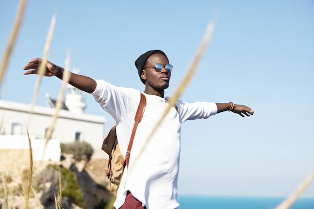 Colpo estivo all'aperto di spensierato giovane viaggiatore felice in piedi in riva al mare con le braccia aperte