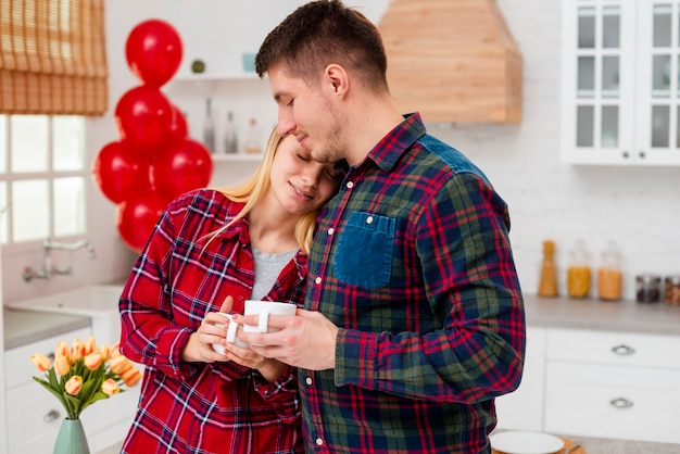 Colpo felice coppia felice in cucina con tazze di caffè