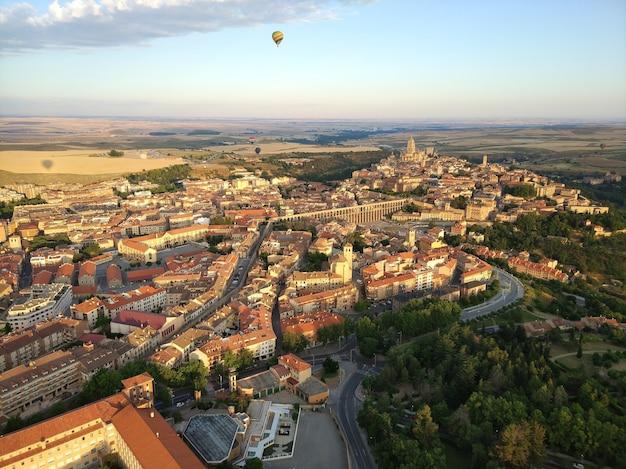 Colpo grandangolare di molti edifici circondati da alberi e un paracadute in aria