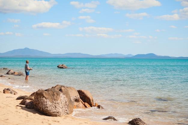 Colpo grandangolare di un uomo che pesca sulla spiaggia sotto un cielo blu chiaro