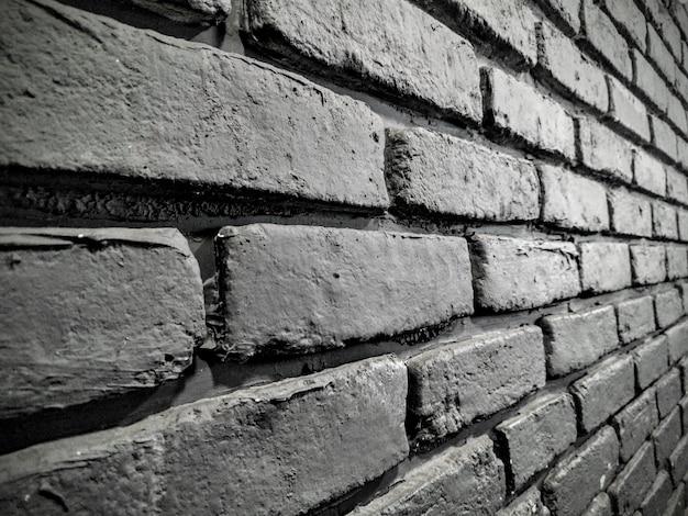 Colpo in scala di grigi di un bellissimo muro di mattoni- perfetto per uno sfondo cool