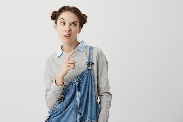 Colpo in testa della donna impertinente 20s che punta il dito indice lateralmente su qualcosa con la faccia accigliata. giovane donna con sguardo scettico a lato gesticolando esprimendo sfiducia. linguaggio del corpo