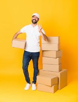Colpo integrale del fattorino fra le scatole sopra isolato giallo felice e contando tre con le dita