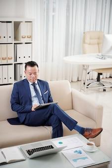 Colpo integrale dell'imprenditore che si siede sul sofà con la compressa digitale