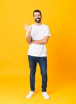 Colpo integrale dell'uomo con la barba sopra fondo giallo isolato che conta cinque con le dita