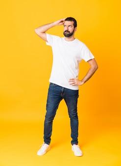 Colpo integrale dell'uomo con la barba sopra fondo giallo isolato che ha dubbi mentre graffiando testa