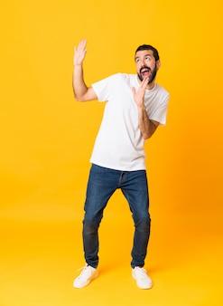 Colpo integrale dell'uomo con la barba sopra fondo giallo isolato nervoso e spaventato