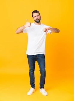 Colpo integrale dell'uomo con la barba sopra giallo che fa segno buono-cattivo giallo. indeciso tra sì o no
