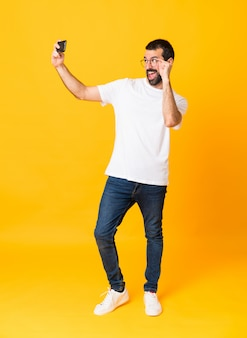 Colpo integrale dell'uomo con la barba sopra giallo isolato che fa un selfie
